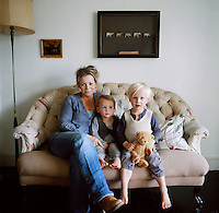 A portrait of Anna Phillips and her two children sitting on a sofa.