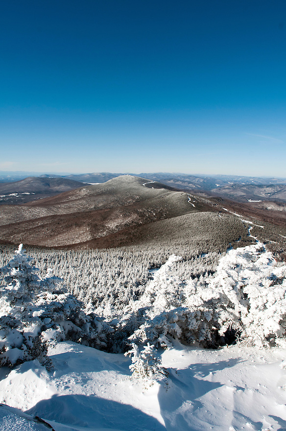 Snow covered trees frame a winter view of Pico Mountain from Killington, Vermont.