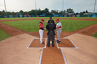 Batavia Muckdogs manager Tom Lawless (left) and Auburn Doubledays manager Rocket Wheeler (right) during the lineup exchange with umpires Rainiers Valero (home) and Jon-Tyler Shaw (field) before a NY-Penn League game on June 14, 2019 at Dwyer Stadium in Batavia, New York.  Batavia defeated 2-0.  (Mike Janes/Four Seam Images)