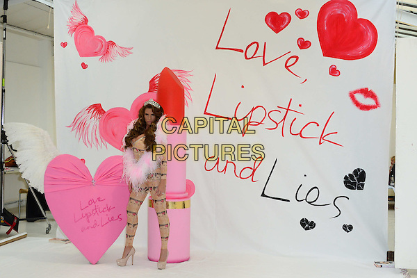 Katie Price (aka Jordan)<br /> At a photocall to launch her autobiography - 'Love, Lipstick And Lies' at The Worx, London, England.<br /> October 22nd, 2013<br /> full length leotard catsuit cover print crown tiara  beige silver pink fur tube book<br /> CAP/BF<br /> &copy;Bob Fidgeon/Capital Pictures