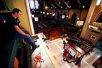 Ogletree & Marshall technician, Ken Hitchcock, looks on from atop the newly installed speaker cabinet as Bob Troeger, director of music and organist for St. Matthew's Church, inspects the keys of the rebuilt, digital pipe organ on July 27, 2015 at St. Matthew's Church in Wheeling, West Virginia. (Jared Wickerham for the Boston Globe)