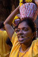 woman  in trance with  spear thrilled through her cheeks while Thaipusam ceremonies inside Batu Caves, Kuala Lumpur, Malaysia, 2012. Thaipusam ceremonies, celebrated by tamile Hindu community in Malaysia, take place  in Sanctuary of Batu Caves at the border of Kuala Lumpur, each year around end of January or beginning of February, according to Hindu moon calendar. The event is paying hommage to Lord Murugan, a spirit or god created by Shiva to lead the army of gods against the army of evil demons, finally defeating the evil spirits. There are many ways to present offerings or sacrifices for this major religious event. Devotees mortify their bodies by carrying heavy kavaris with spears fixed in their skin or fruits, flowers and little post with holy milk fixed with hooks in their skin, ascending the stairways to the sanctuary in trance, `followed by assistant  taking care and musicians playing loud and fast rhythmic trance music.  Many families shave their head in a ritual before ascending the stairways, as part of rituals to obtain salvation for their ancestors.