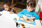 Education preschool 3-4 year olds boy and girl sitting side by side playing separately girl writing and boy playing with wooden puzzle