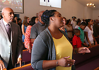 A woman sings during a service at the Mt. Zion Baptist Church where Virginia Governor Terry McAuliffe spoke about the tragedies that unfolded after Unite the Right rally  in Charlottesville, Va. Photo/Andrew Shurtleff