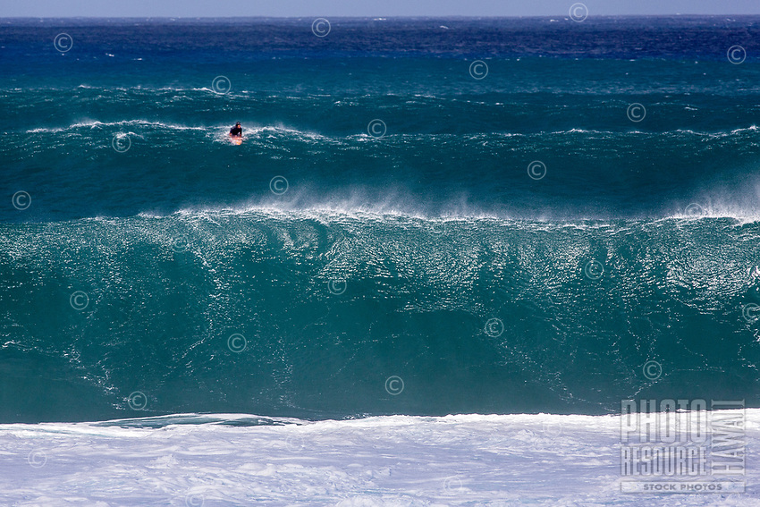 A lone surfer in the midst of a set of large waves at Pipeline (off of 'Ehukai Beach Park), North Shore, O'ahu.