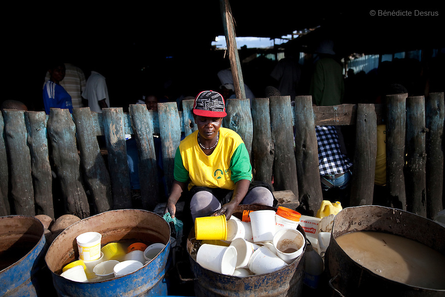 A Kenyan woman washes plastic bucket at the Madiaba Busaa Club in a Nairobi slum on April 21, 2013. Busaa is a traditional fermented beer made by crudely fermenting maize, millet, sorghum or molasses. At Kshs 35 per liter it is much cheaper than a Kshs120 half-liter bottle of commercial beer. The local brew was legalised in 2010 and since then busaa clubs have become increasingly popular. Drinking is on the rise in Kenya, especially among young people. Photo by Benedicte Desrus