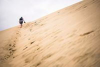 Tourist climbing Te Paki Sand Dunes on 90 Mile Beach, Northland, New Zealand