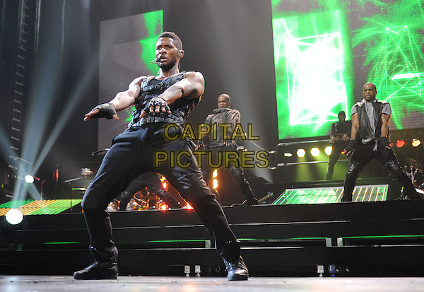 "USHER RAYMOND .Usher performs live at Honda Center during his ""OMG Tour 2010"" held at The Honda Center in Anaheim, California, USA. .November 14th, 2010.stage concert live gig performance music full length black leather hands arms sleeveless jeans denim singing fingerless gloves funny dancing  backup dancers .CAP/RKE/DVS.©DVS/RockinExposures/Capital Pictures."