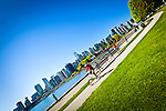 Stanley Park, Vancouver, B.C, Canada on a sunny day in early summer. A bicyclist rides by the water front. The downtown skyline is in the background.