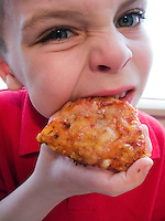 Young boy bites into slice of hot pizza