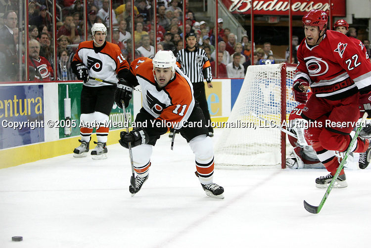 Philadelphia's Jonathan Sim (11) and Carolina's Mike Commodore (22) chase after the puck on Friday, October 28, 2005, at the RBC Center in Raleigh, North Carolina during a regular season NHL game. The Carolina Hurricanes defeated the Philadelphia Flyers 8-6.