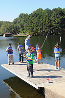 NWA Democrat-Gazette/FLIP PUTTHOFF <br /> Fourth-grade students from R.E. Baker Elementary in Bentonville fish at Lake Windsor with help from Gary Henderson of the Fly Tyers. The group has been hosting the fishing event for more than 10 years, Henderson said.