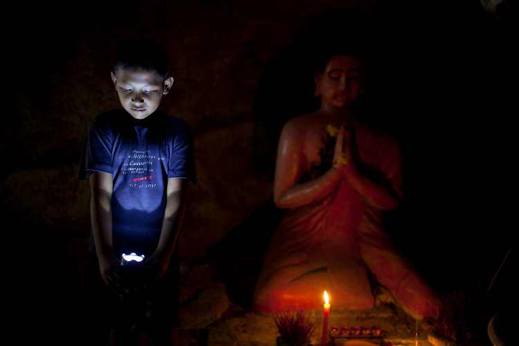 A young your guide leads the way through a network of caves with buddhist statues outside the resort town of Kep, Cambodia. <br /> <br /> Photos &copy; Dennis Drenner 2013.
