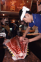 A trader processes the meat on a large tuna at  Tsukiji Wholesale fish market n Tokyo, Japan April 21st 2006