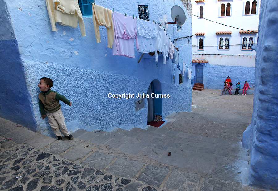 """A little boy laughs at something at the top of one of the many stairways in Chefchaouen, Morocco, whose """"medina"""" (old city) is famous for its striking blue walls."""