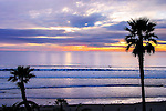Palm Trees Frame The Lazy Surf Of The Pacific Ocean At Sunset Near San Diego California, USA