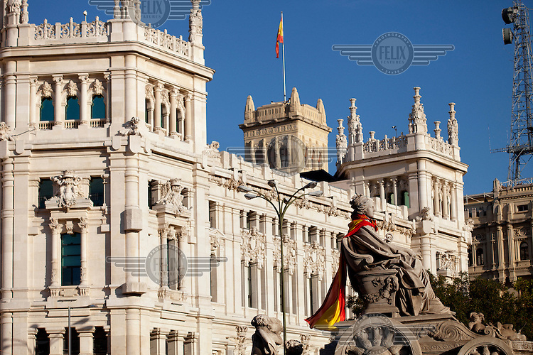 The national flag is wrapped around the neck of the Cibeles statue outside CIty Hall in Madrid.