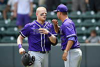 Catcher Cameron Whitehead (16) of the Furman Paladins is congratulated by pitcher Grant Schuermann (37) after scoring a run in a game against the UNC Greensboro Spartans at the Southern Conference Baseball Championship on Saturday, May 27, 2017, at Fluor Field at the West End in Greenville, South Carolina. UNCG won, 12-8. (Tom Priddy/Four Seam Images)