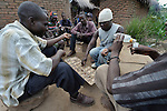 Men play a game, and drink alcohol, in Karonga, a town in northern Malawi.