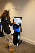Kingston University, Kingston upon Thames,. Female student using a library self-service borrowing point.