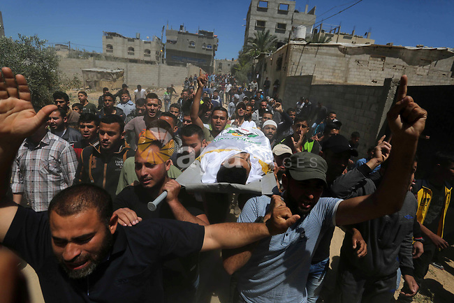 Mourners carry the body of Palestinian Abdullah Abdelal, 24, who was shot dead by Israeli forces at the Israel-Gaza border, during his funeral in Rafah in the southern of Gaza strip, on May 11, 2019. Photo by Ashraf Amra
