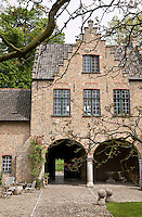 View of the cobbled courtyard and the mellow brick facade of the manor house