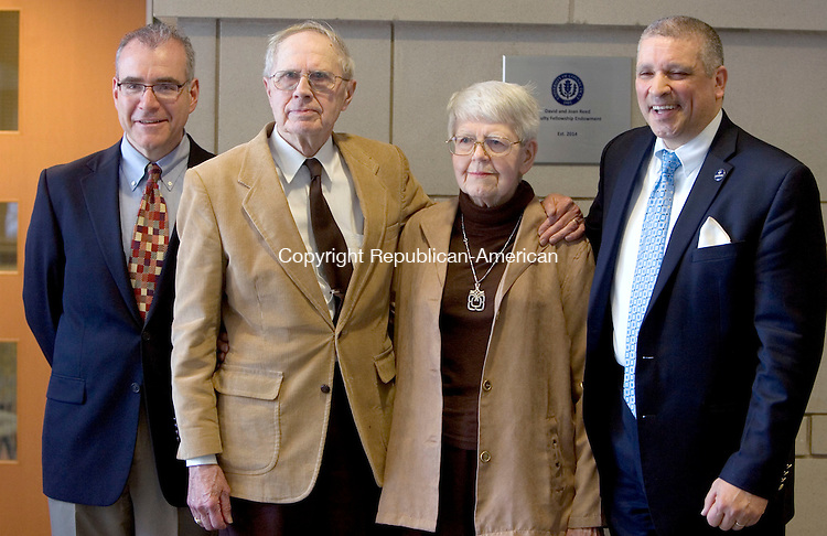 WATERBURY CT. 13 April 2015-041315SV07-From left, Mitchell Green, professor, David and Joan Reed of Middlebury and William Pizzuto, Director of Waterbury UConn, stand by a plaque stating the David and Joan Reed Faculty Fellowship Endowment outside the community room at the school in Waterbury Monday. <br /> Steven Valenti Republican-American