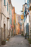 FRANCE, Villefranche sur Mer, a path in between two rows of yellow and orange buildings, with laundry lines outdoors