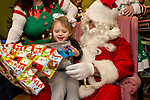 TORRINGTON, CT. 20 December 2019-122019BS09 - Rai Lynn, 5, of Torrington, left, unwraps a gift given to her by Santa, during a visit by Santa at the FISH of Northwestern Connecticut Homeless Shelter in Torrington on Friday. Bill Shettle Republican-American