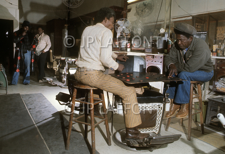 December 1976. Americus, Georgia. Unemployed people playing checkers in a barber shop.