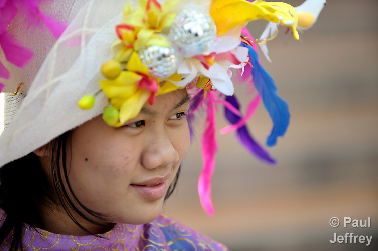 Tiwarin Duangkam participates in a dance group organized by the Hualin Buddhist Temple in the northern Thailand village of Toong-sa-tok. The group, which performs for weddings and other celebrations and uses the proceeds for its members' educational expenses, includes orphans and other vulnerable girls, many of them affected by HIV and AIDS. Tiwarin Duangkam, 13 and HIV negative, lost her mother to AIDS and lives with her HIV positive father...
