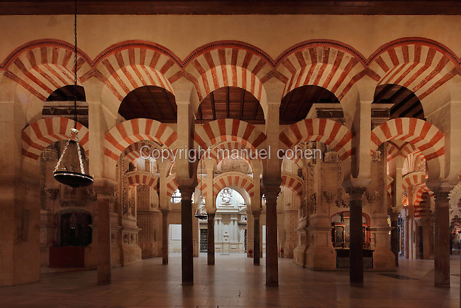 Hypostyle prayer hall, area built under Prince Abd Al-Rahman II, begun 832, in the Cathedral-Great Mosque of Cordoba, in Cordoba, Andalusia, Southern Spain. The hall is filled with rows of columns topped with double arches in stripes of red brick and white stone. The retroquire of the catholic cathedral is glimpsed through the columns. The first church built here by the Visigoths in the 7th century was split in half by the Moors, becoming half church, half mosque. In 784, the Great Mosque of Cordoba was begun in its place and developed over 200 years, but in 1236 it was converted into a catholic church, with a Renaissance cathedral nave built in the 16th century. The historic centre of Cordoba is listed as a UNESCO World Heritage Site. Picture by Manuel Cohen