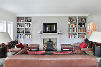 A leather sofa, two matching footstools and a pair of armchairs face a wood burning stove and a flat screen television in a sitting room