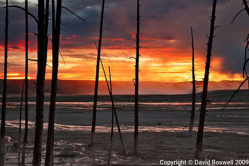 The sun turns the sky to fire as it sets over the Lower Geyser Basin in Yellowstone National Park.