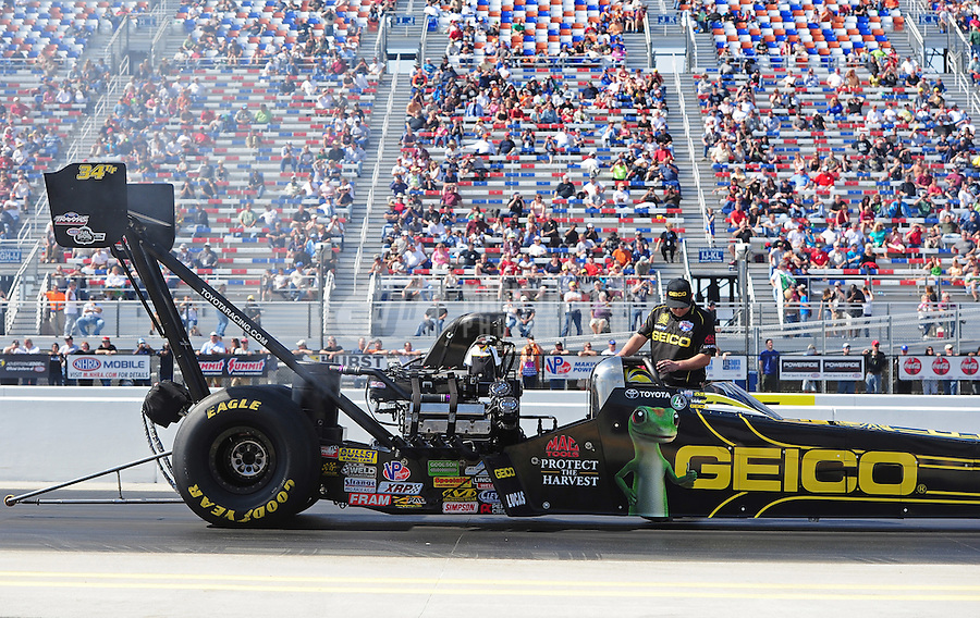 Apr. 13, 2012; Concord, NC, USA: A crew member prepares to back up NHRA top fuel dragster driver Morgan Lucas during qualifying for the Four Wide Nationals at zMax Dragway. Mandatory Credit: Mark J. Rebilas-