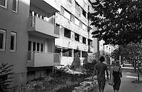 Mostar, due giovani e un edificio in rovina danneggiato durante la guerra, con fori di proiettile nel muro, tra palazzi nuovi --- Mostar, a young man and a young woman passing by the ruin of a building damaged during the war, with bullet holes in the wall, between new buildings