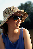 La Lope, Gabon. French woman tourist in straw hat with rain forest behind.
