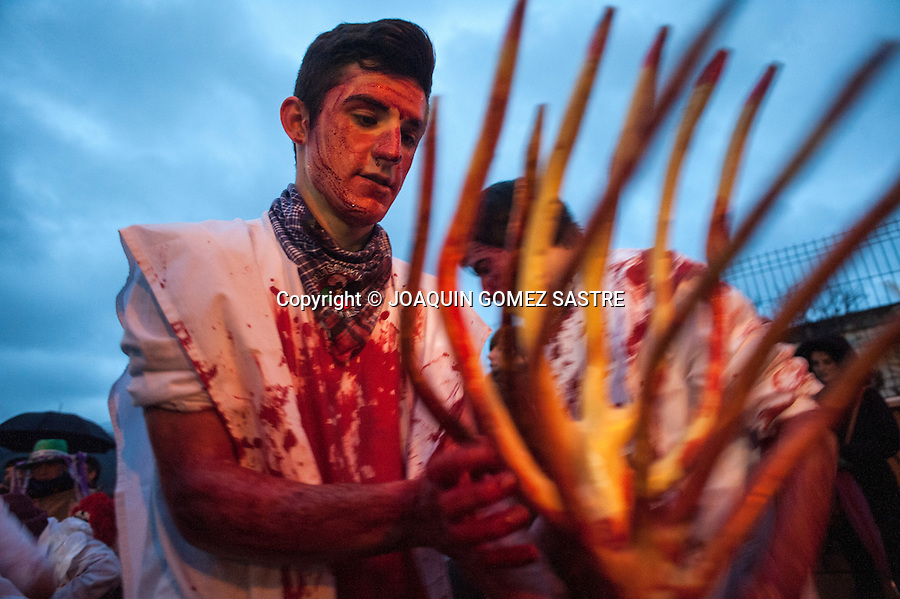 One participant in the carnival of Alsasua smeared his trident with cow blood before the parade through the streets of the town