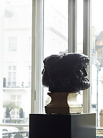 In the dining room, a double-headed sculpture is strategically placed on a pedestal at the front window.
