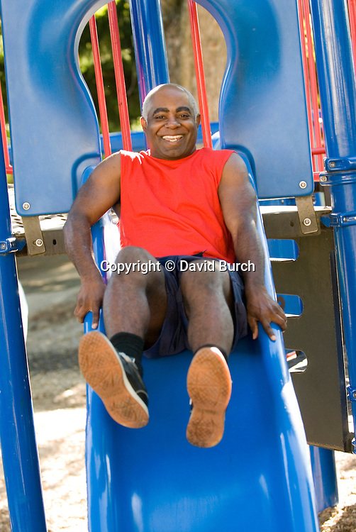 African American man on playground slide, smiling