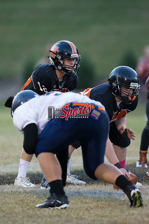 Sam Walker (12) of the Northwest Cabarrus Trojans lines up under center Isaac Haywood (72) during first half action against the Carson Cougars at Trojan Stadium October 22, 2015, in Concord, North Carolina.  The Cougars defeated the Trojans 21-20.  (Brian Westerholt/Sports On Film)