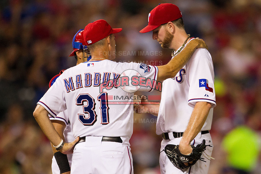 Texas Rangers pitching coach Mike Maddux #31 talks on the mound with pitcher Scott Feldman #39 during the Major League Baseball game against the Baltimore Orioles on August 21st, 2012 at the Rangers Ballpark in Arlington, Texas. The Orioles defeated the Rangers 5-3. (Andrew Woolley/Four Seam Images).