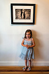LILY CARLSON, 5, of Rock Point, is under a photo of herself, 'Uncaged' by Jennifer Carlson, at the Fotofoto Gallery Opening Reception of the 2013 'Under The Influence' Student Invitational Exhibition. On display were images of 29 photography students of instructors from fotofoto, the event venue.