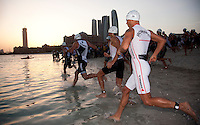 12 MAR 2011 - ABU DHABI, UAE - The Elite Men's field run into the water at the start of the Abu Dhabi International Triathlon .(PHOTO (C) NIGEL FARROW)