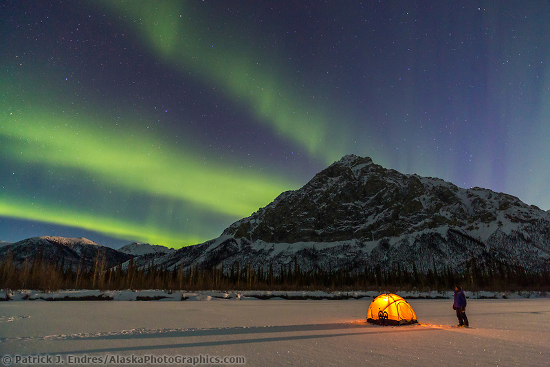Man stands by glowing yellow tent and watches the northern lights dance over Mount Dillon, Brooks Range, Alaska.