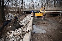 Workers excavate a walkway to add a pump system for a bike path adjacent to a small creek that frequently overflows its banks flooding the path. The hole digging process was complicated by a heavy storm several days earlier that covered the hole and path in several feet of water damaging pieces of equipment and slowing the crew's progress.