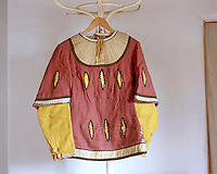 A red tunic in the Tudor style with a fake under-shirt sewn into it and appliqued shapes designed to look like slashes through which can be seen the yellow garment underneath