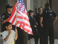 Phoenix, Arizona, USA-- A boy participating in a protest against Arizona's new immigration law stands with an American flag as police officers watch the protest in the background. (Pat Shannahan/ The Arizona Republic)