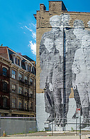 "New York, USA - Street Mural entitled ""Ellis Island"" a tribute, by French Aetist JR,  to the millions of Immigrants who passed through Ellis Island."