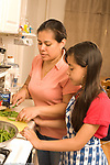 11 year old girl in kitchen with mother learning to cook in kitchen, cutting vegetable, green beans